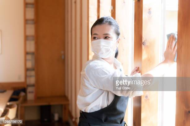asian young adult woman wearing a mask, carefully wipe and enthusiastically disinfect in preparation for opening - catering building stock pictures, royalty-free photos & images