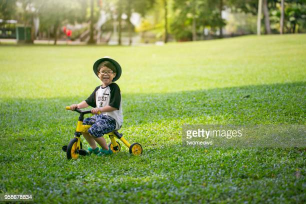 asian young boy in leisure activity. - tricycle stock pictures, royalty-free photos & images