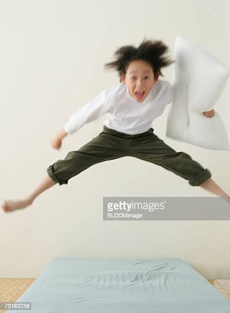 Asian young boy jumping on bed