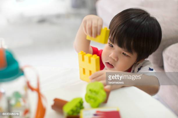 Asian young boy playing building block.