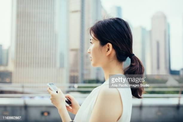 アジアの若いビジネスウーマンが、上海・上海のルジアズイ金融街の金融超高層ビルの前で屋外でスマートフォンを使用 - young women ストックフォトと画像