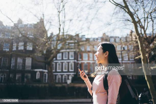 asian young cheerful woman looking up to the sky while holding her smartphone on the street - politics and government stock pictures, royalty-free photos & images