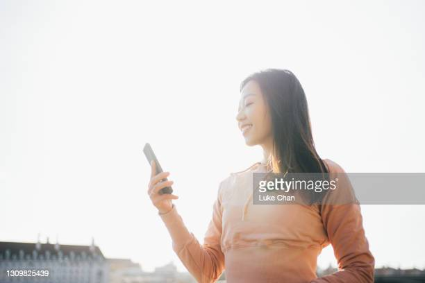asian young cheerful woman using her smartphone by the river side - politics and government stock pictures, royalty-free photos & images