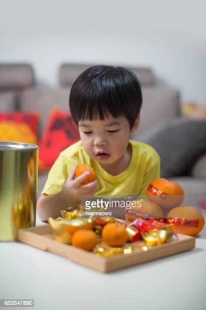 Asian young child boy with mandarin orange in festive season background.
