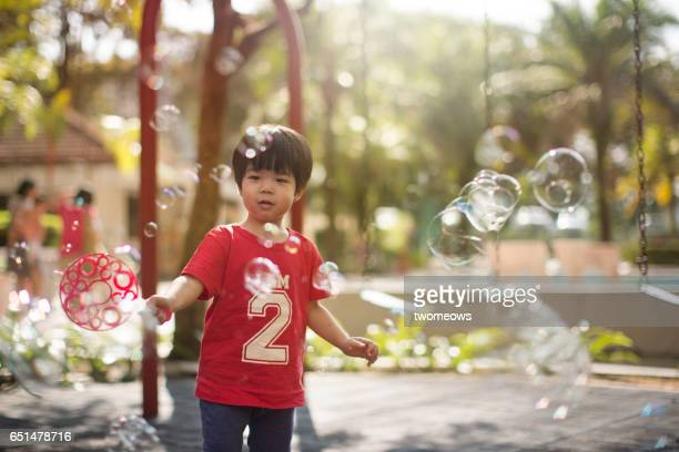 Asian young child playing soap bubbles in playground.
