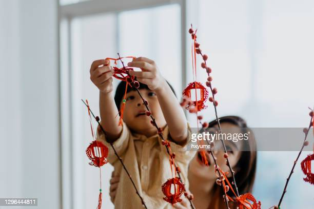 asian young chinese boy helping mother to hang chinese new year decoration - chinese new year stock pictures, royalty-free photos & images