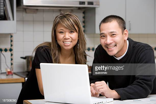 Asian Young Couple Using Laptop in Home Kitchen, Copy Space
