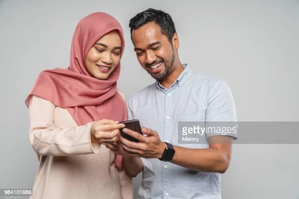 pareja joven asiático con teléfono inteligente - malasia fotografías e imágenes de stock