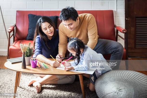 asian young family with one child drawing together at home with happiness - family at home stock pictures, royalty-free photos & images