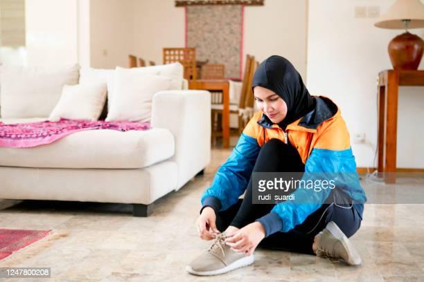 jeune athlète féminine asiatique portant un hijab de sport et attachant ses lacets - hijab feet photos et images de collection