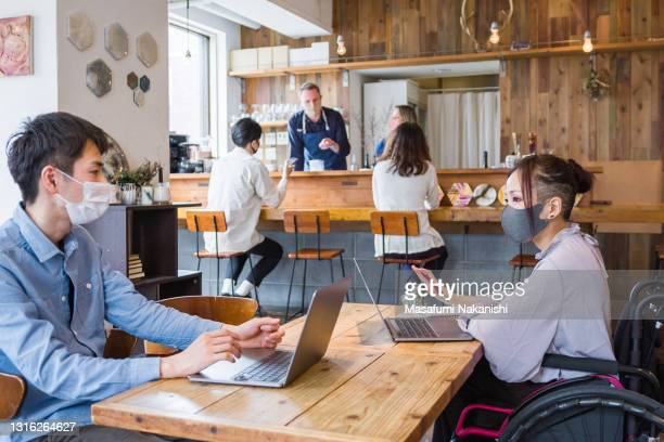 asian young female entrepreneur in a wheelchair having a business conversation with her team in a local space - physical disability stock pictures, royalty-free photos & images