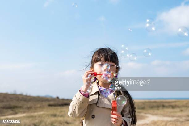 Asian Young Girl Having Fun and Blowing Bubbles Outdoors