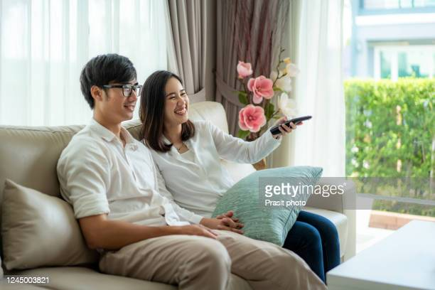 asian young loving couple sitting and watching tv in a comfortable couch in the living room at home. family lifestyle relax and recreation concept - mood stream stock pictures, royalty-free photos & images