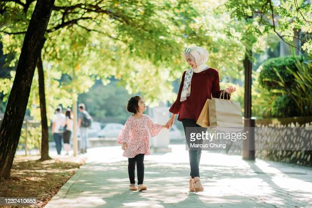 asian young malay smiling mother carrying shopping bags and holding daughter's hand walking on the city street - east asian ethnicity stock pictures, royalty-free photos & images
