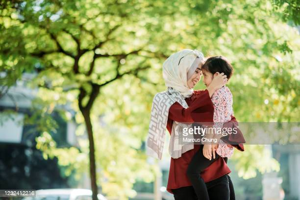 asian young malay smiling mother holding up her daughter and head to head at city street - east asian ethnicity stock pictures, royalty-free photos & images
