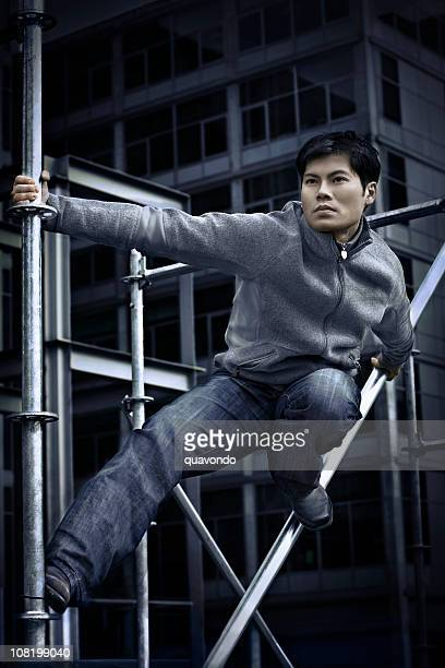 Asian Young Man as Ninja on Downtown Building, Copy Space