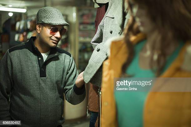 Asian young man checking garment for shopping in market.