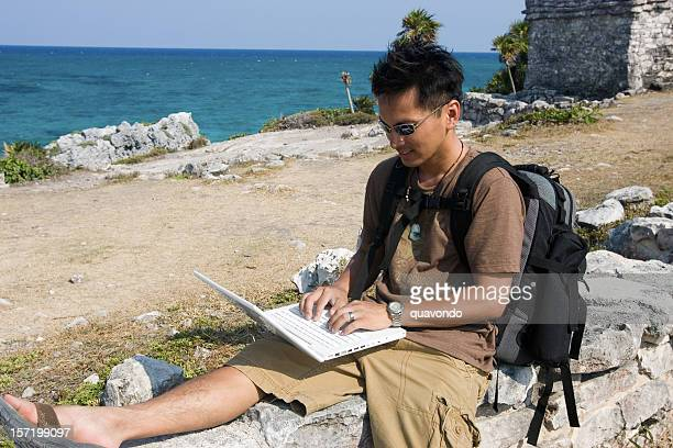 Asian Young Man Hiking in Mexico Using Laptop, Copy Space