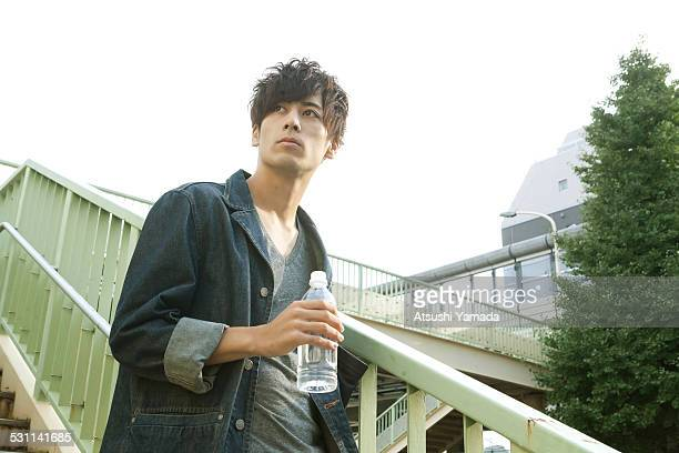 Asian young man holding water,standing on stairs