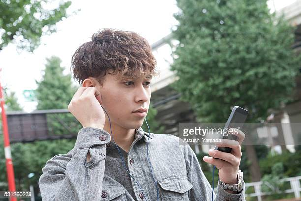 Asian young man listening to music on street