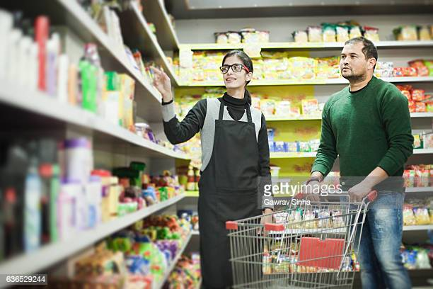 Asian young man shopping at supermarket and female staff helping.