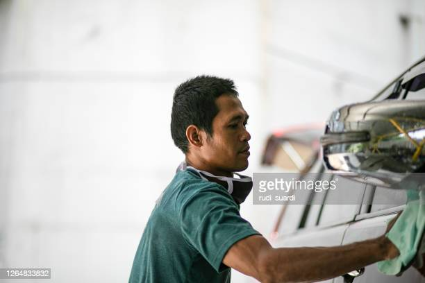 asian young man washing and cleaning car - car wash brush stock pictures, royalty-free photos & images