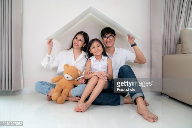 asian young parents keeping their hands close forming roof over their daughter while sitting on the floor of living room at home. concept of housing for young family. - wohngebäudeversicherung stock-fotos und bilder