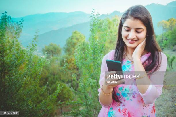 Asian young woman browsing images in smartphone at scenic view.