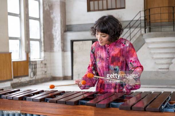 asian young woman dressed in pink plays marimba in ruins - musical instrument stock pictures, royalty-free photos & images