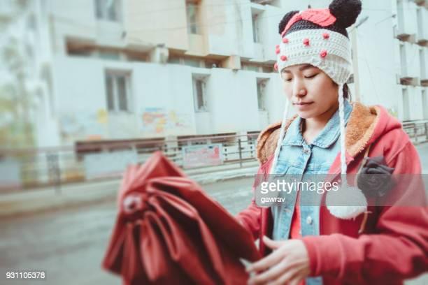 Asian young woman folding umbrella while walking on roadside.