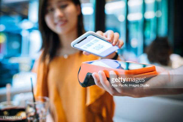 asian young woman paying with smartphone in a cafe. - paying stock pictures, royalty-free photos & images