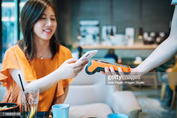 asian young woman paying with smartphone in a cafe. - credit card purchase stock pictures, royalty-free photos & images