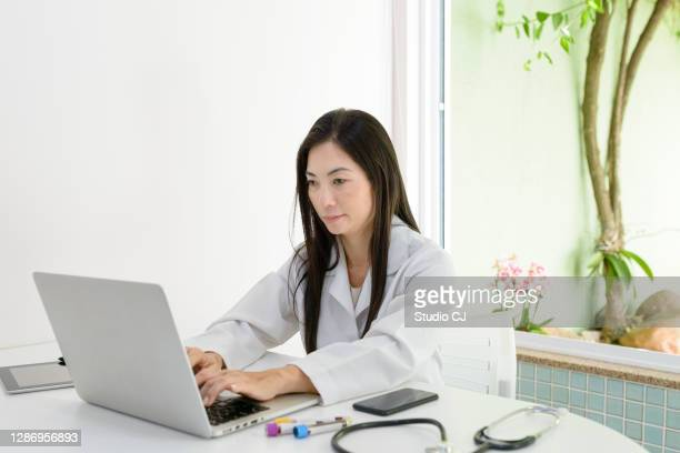 asian young woman performing data entry on portable device - portable information device imagens e fotografias de stock