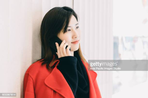 asian young woman plays with mobile phone in modern city, shanghai,china - studio city stock pictures, royalty-free photos & images
