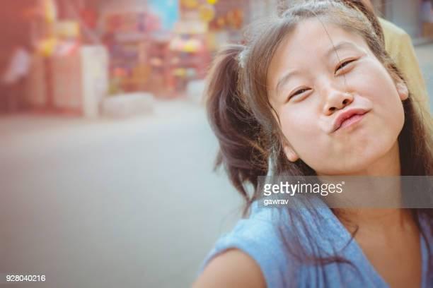 Asian young woman pouting at camera.