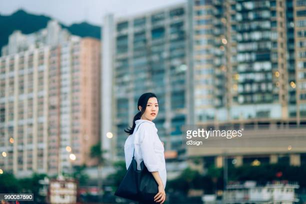 asian young woman standing against hong kong city skyline looking far away with confidence and positive emotion - 肩ごしに見る ストックフォトと画像