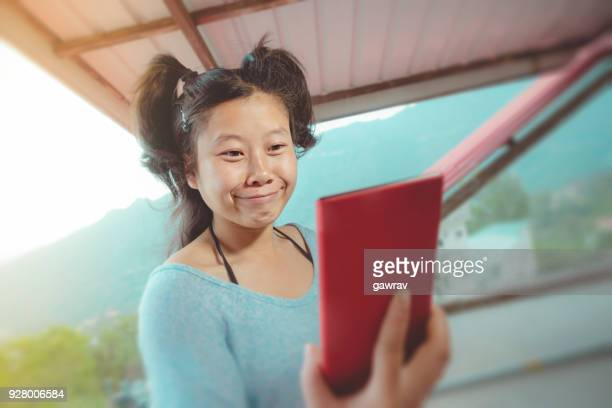 Asian young woman taking funny selfie.