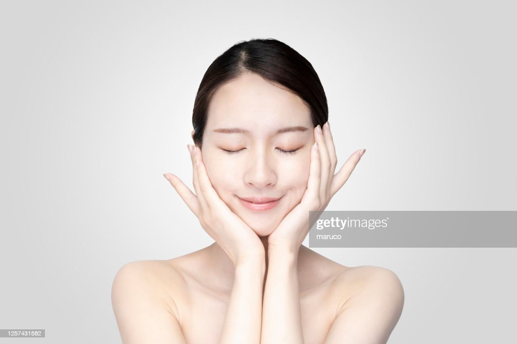 Asian young woman touching face with relaxed expression : Stock Photo