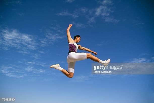 Asian-American man doing long jump at track meet. California, USA.