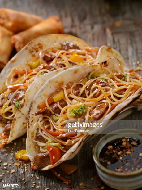 asian/mexican fusion - teriyaki beef and noodle tacos - tortilla flatbread stock photos and pictures