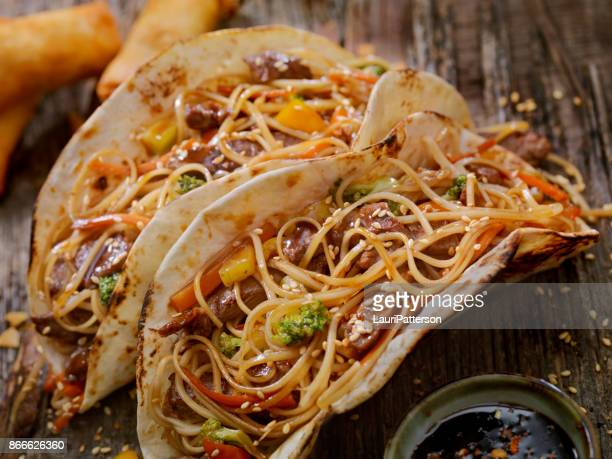 asian/mexican fusion - teriyaki beef and noodle tacos - crucifers stock pictures, royalty-free photos & images