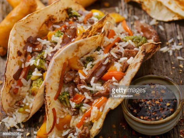 asian/mexican fusion - teriyaki beef and rice tacos - tortilla flatbread stock photos and pictures