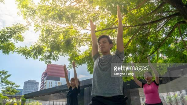 屋外で立っているヨガのポーズをしているアジア人 - extra long ストックフォトと画像