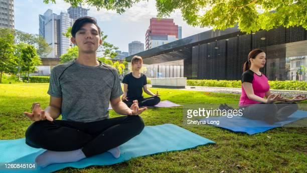 屋外でヨガをしているアジア人。ヘルスケアとボディケアの概念 - extra long ストックフォトと画像