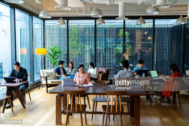 asians millennials busy working in co-working space. - singapore stock pictures, royalty-free photos & images