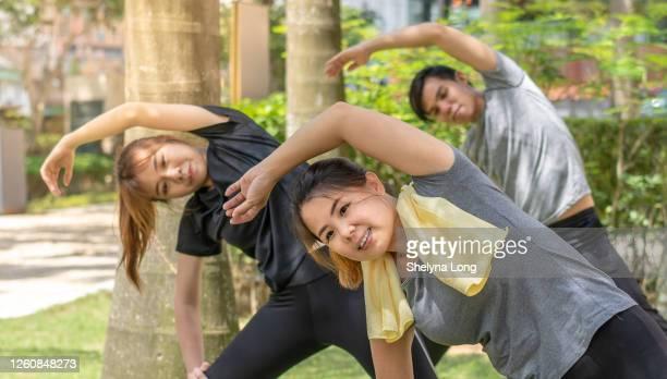 屋外で運動する前にウォーミングアップするアジア人 - extra long ストックフォトと画像