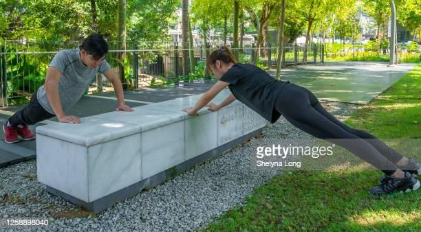 アジアの若いアスリートの腕立て伏せは屋外でワークアウト - extra long ストックフォトと画像