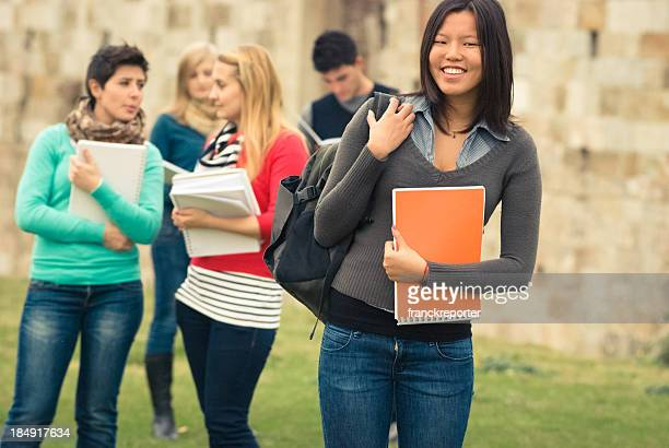 Asiatic female college student outdoors holding a book