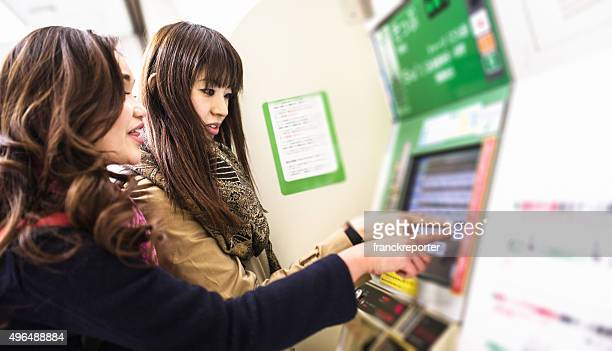 アジアご友人とご一緒に、洗濯機でチケット購入 - 鉄道駅 ストックフォトと画像