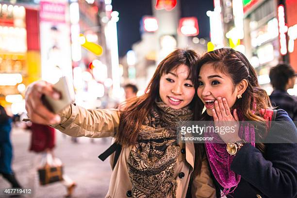Asiatic friends togetherness on Tokyo by night take selfie